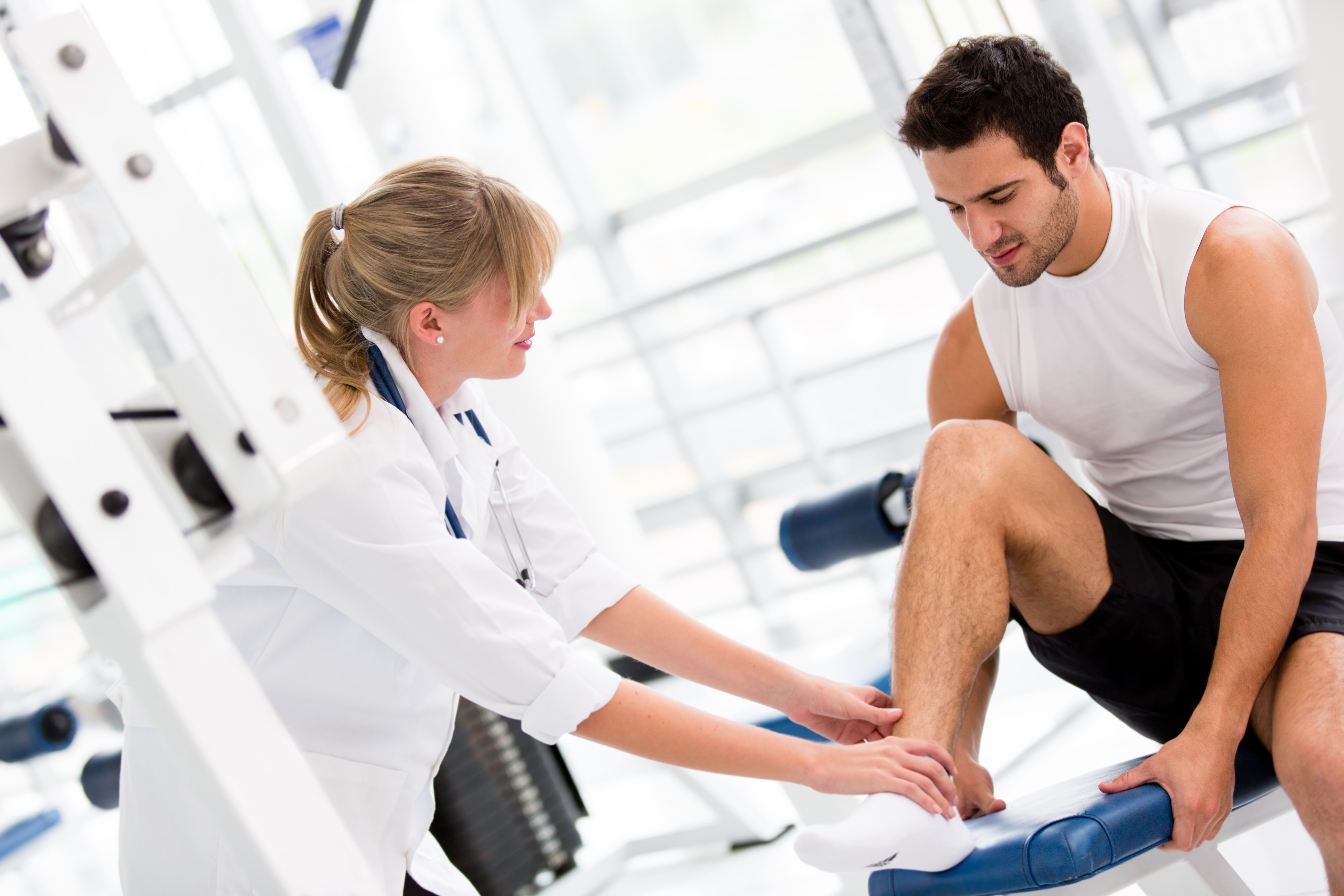 Injured man at the gym feeling pain in his ankle